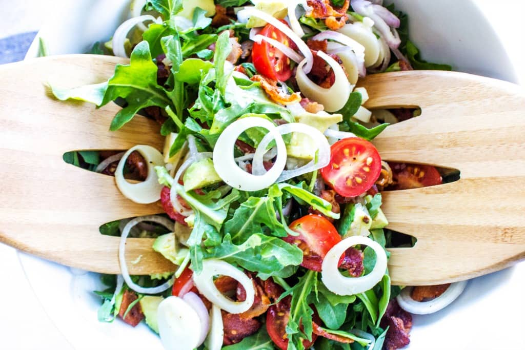 ARUGULA AND HEARTS OF PALM SALAD White bowl and wooden salad spoons
