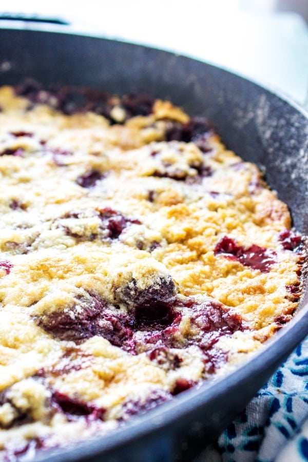 This CHERRY COBBLER RECIPE finished dick in iron skillet on blue napkin