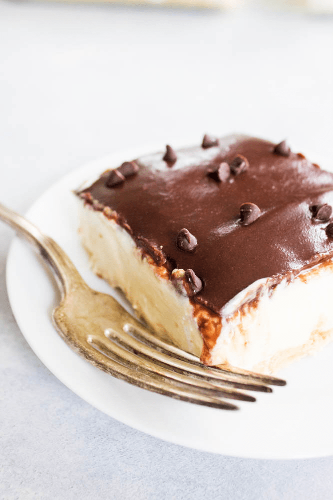 NO BAKE BOSTON CREAM PIE CHEESECAKE on a white plate with fork and topped with chocolate chips.