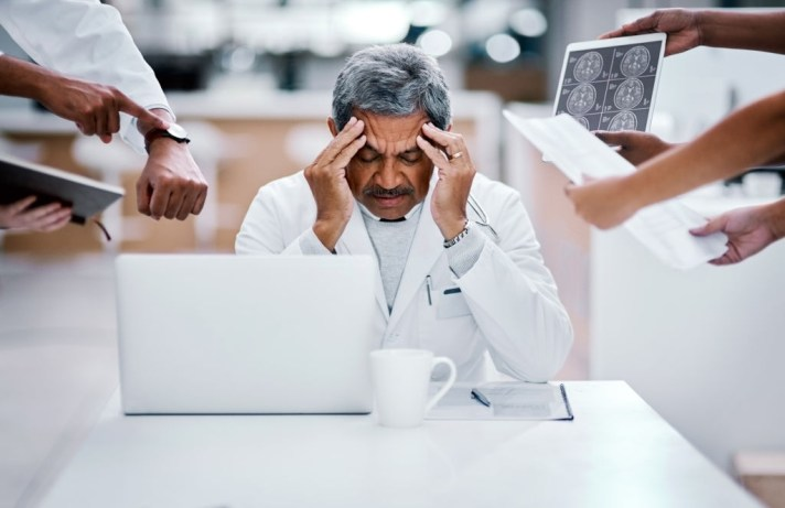 Shot of a mature doctor looking stressed out in a demanding work environment