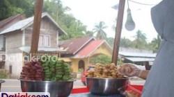 Pedagang Kelok Pinyaram, Fitri, mengambilkan Pinyaram untuk pelanggannya. Pinyaram adalah makanan khas Padangpariaman yang dibuat dengan cara digoreng. (Foto: Datiak.com)