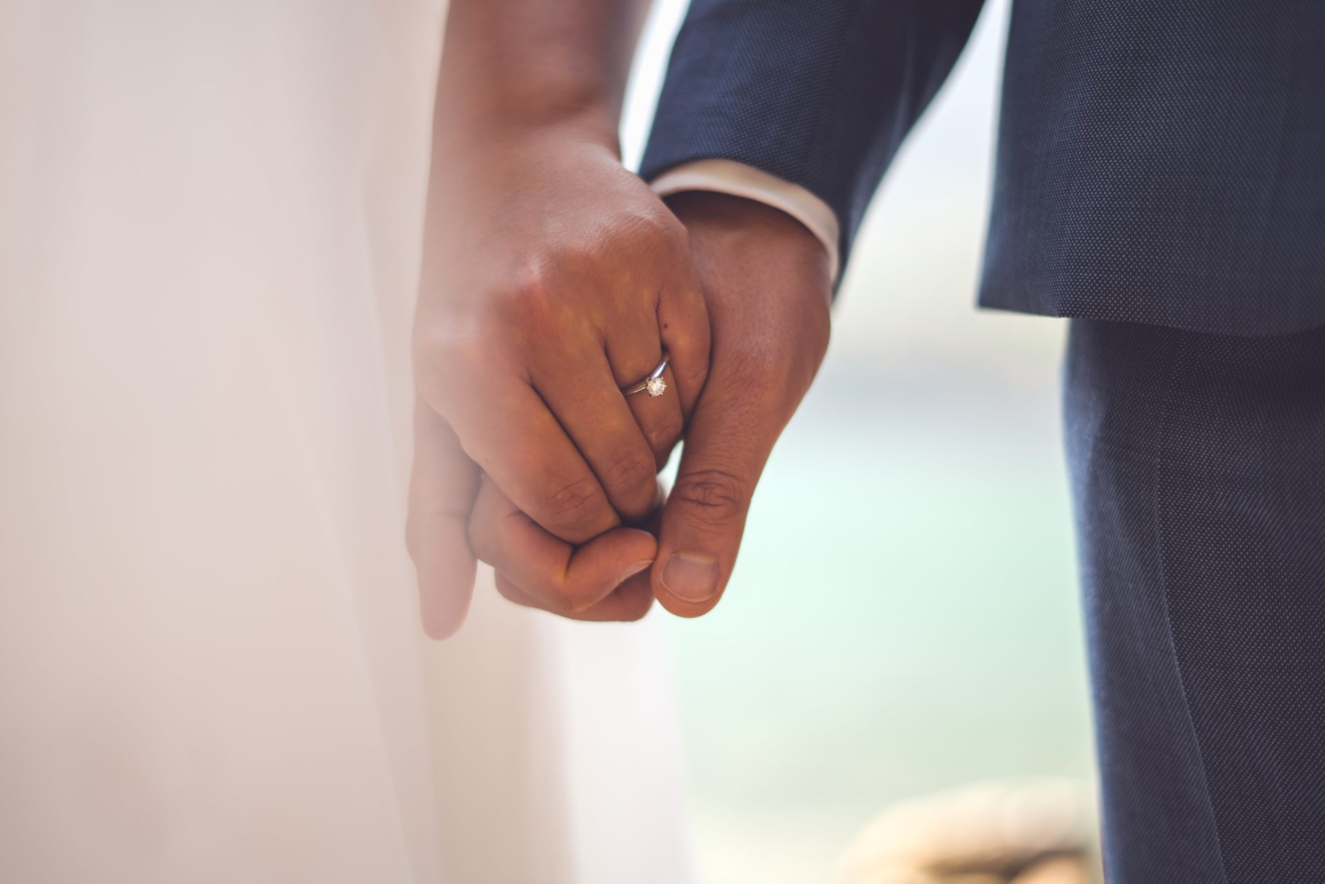 Man and woman holding hands at wedding