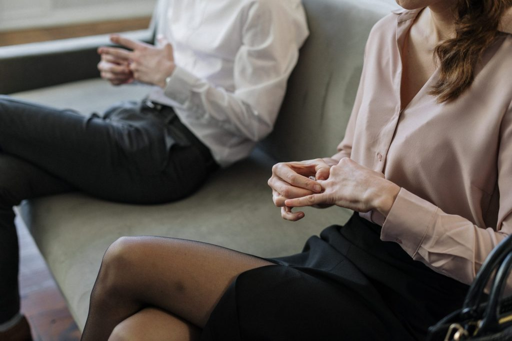 Man and Woman sitting on couch uncomfortably