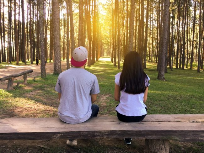 Couple sitting side by side outside