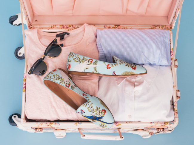 Pink luggage with sunglasses and shoes for vacation packing