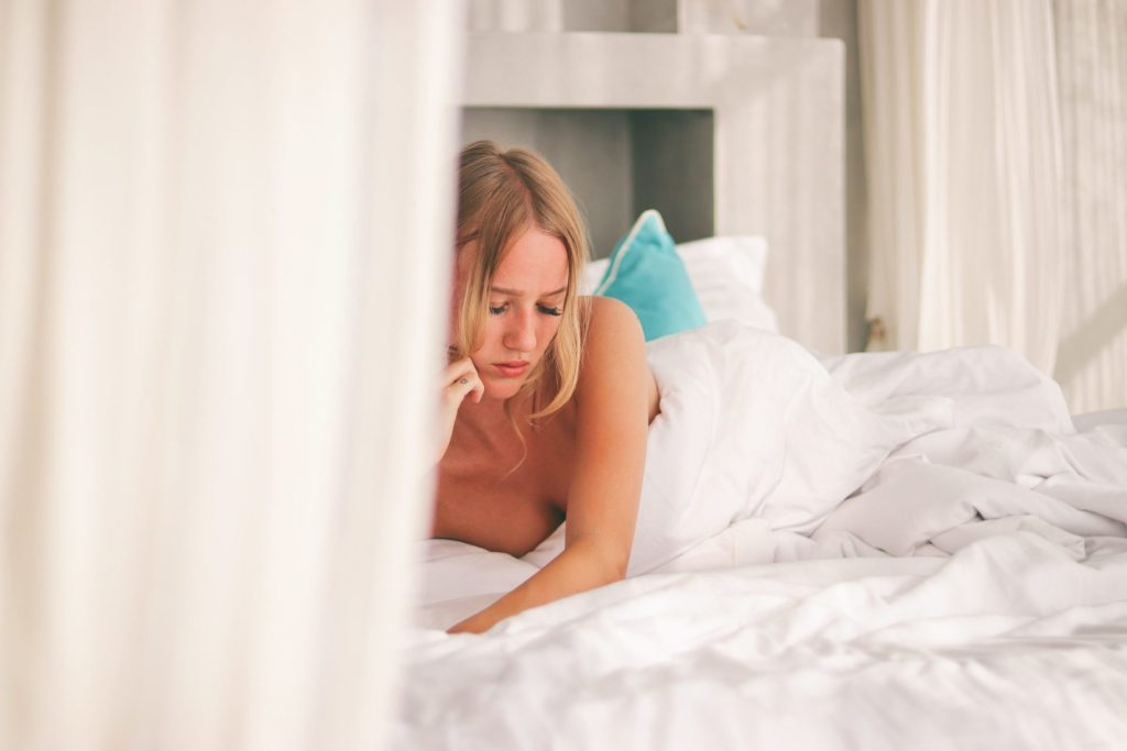 Woman laying on stomach on bed looking sad