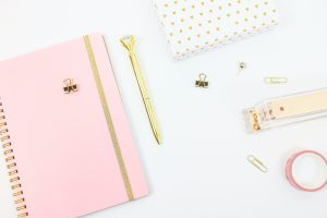 pink notebook on white desk flat lay