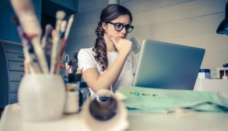 Woman sitting in front of computer looking stressed