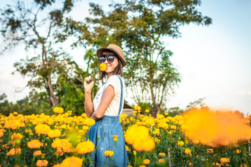 Woman smelling a flower in a field of yellow flowers