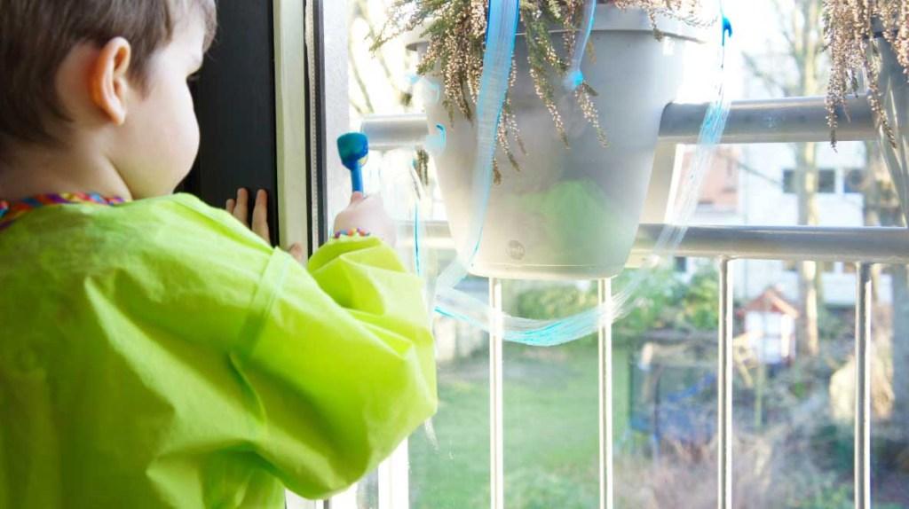 Malen an der Fensterscheibe mit Fingerfarbe