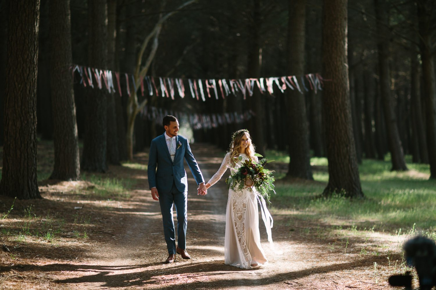 Bride and groom walking together through beautiful light in Burbrook forest Kuitpo