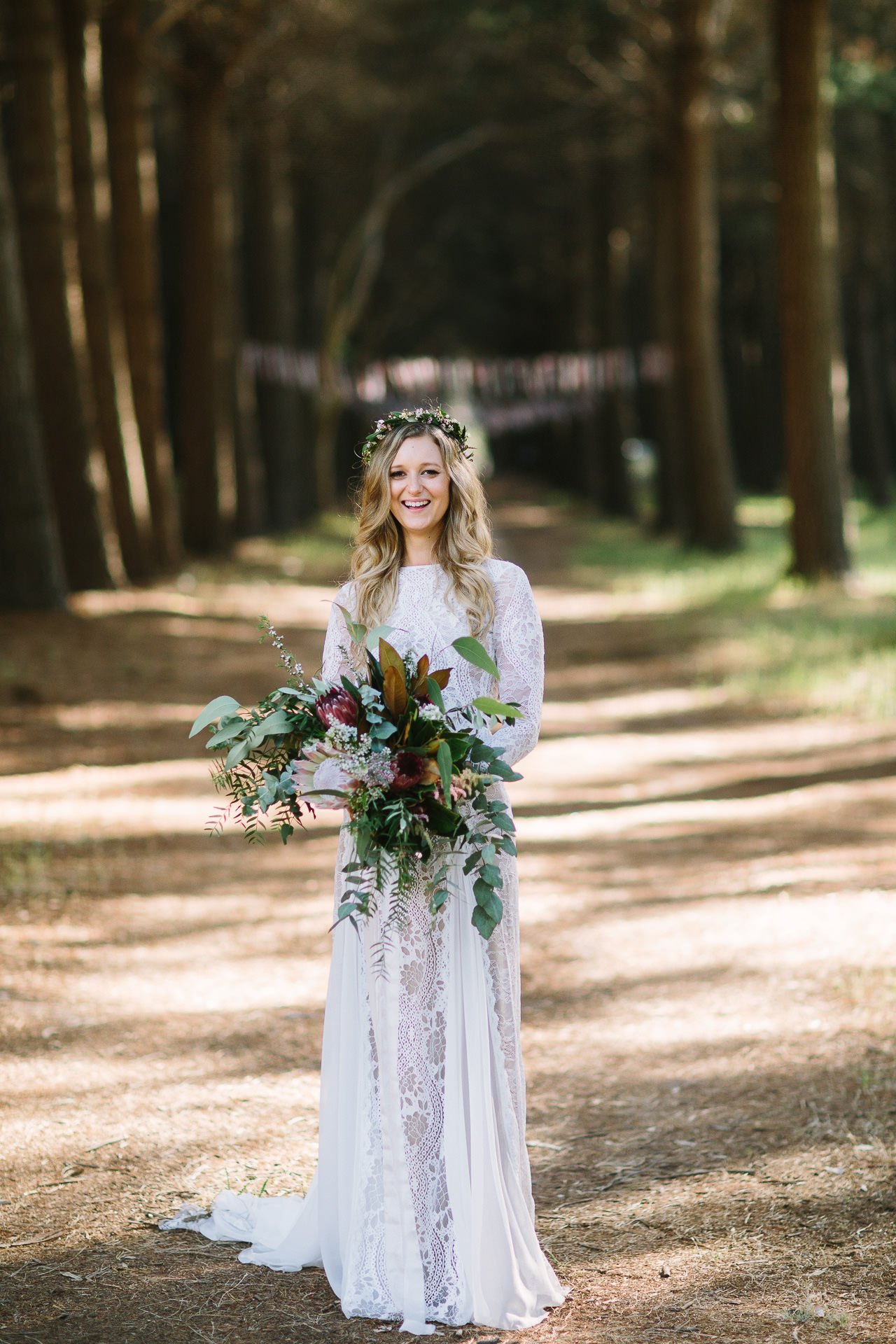 Happy bride in Kuitpo forest holding bouquet wearing grace loves lace wedding dress and flower crown