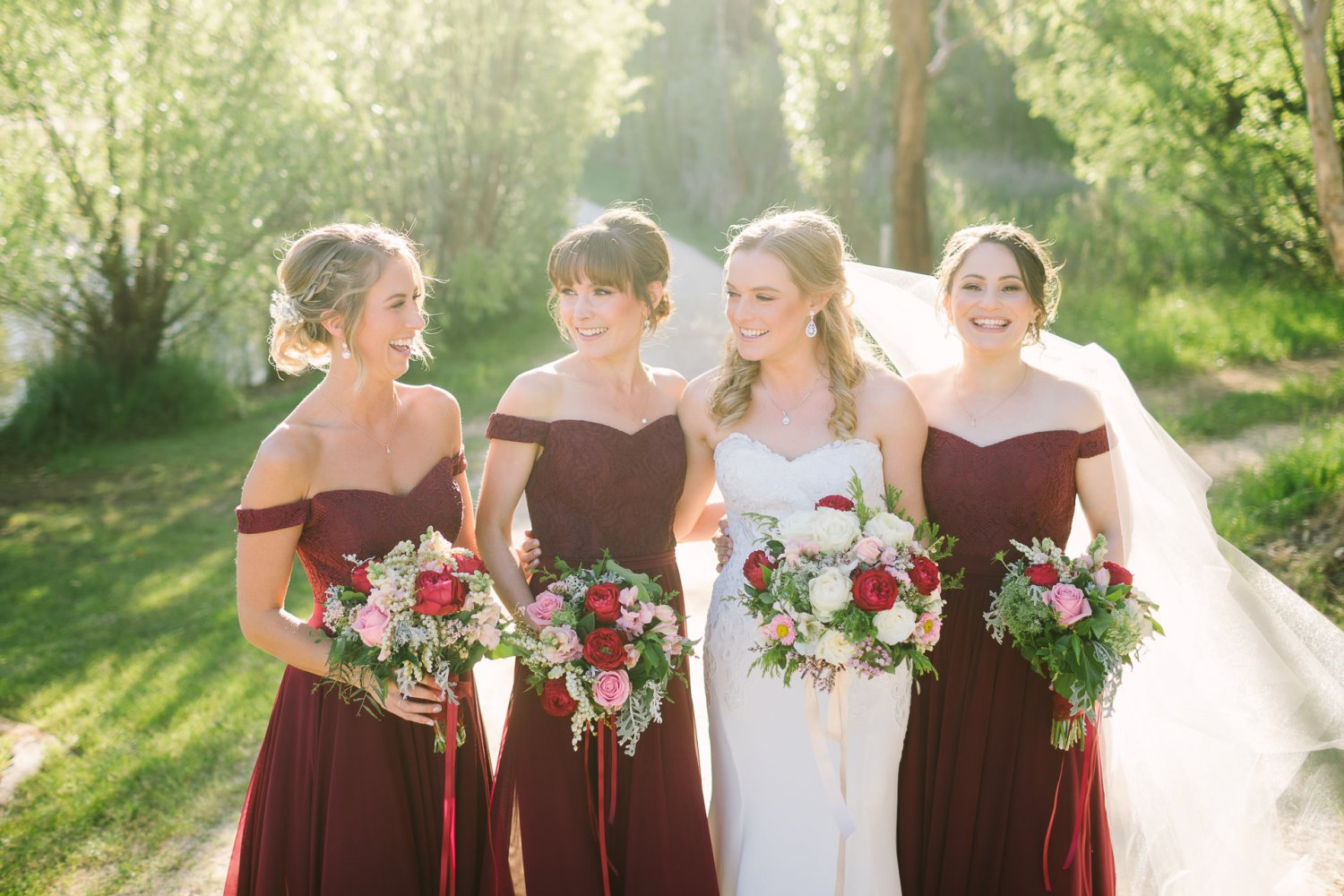 bridesmaids laughing together uposed and natural with bride and flowers in hand at K1 winery