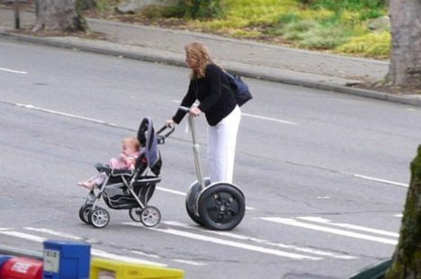 A woman pushing a stroller while riding her Segway because she is too fucking lazy to walk a block.