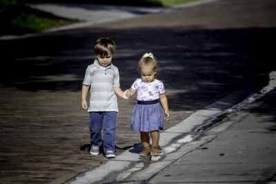 Two toddlers walking hand and hand