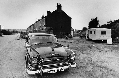 Vintage black and white print scan 1972 image of old Humber car and trailer outside condemned terrace of houses gypsy encampment at Anston near Sheffield