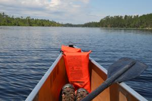 In a canoe in the boundary waters in July with a life vest, sandals, and a paddle.