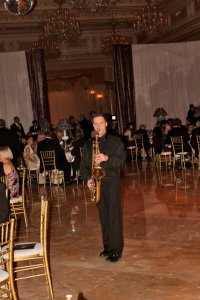 David Turner plays sax in the middle of a ballroom floor, for a high-end event.