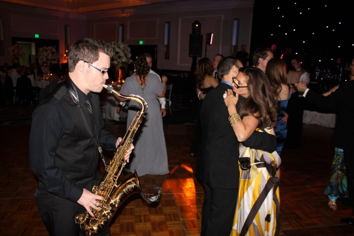 David Turner, dressed in black, strolls while playing saxophone for some wedding guests in Florida.
