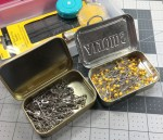 Various Pins stored in recycled mint tins.