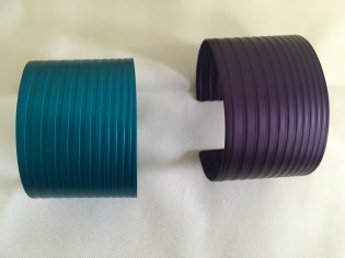 Two cuff bracelets, one teal and one purple by Marvin Shafer