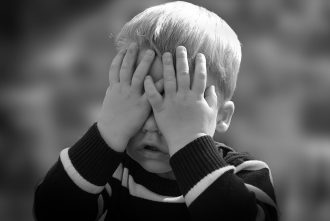 Photograph of a young boy covering his face