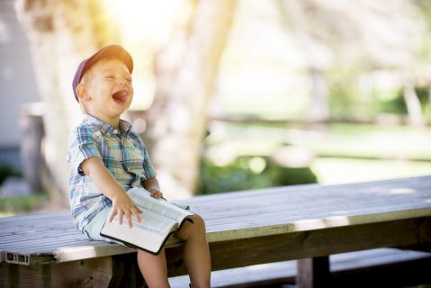 Photograph of laughing child with a book