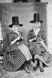 two women in traditional dress knitting