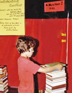Boy trying to stack 25 books for the 25th anniversary of the Columbia Public Library.