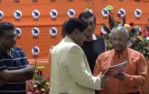 Redactievoorzitter Sonny Hira overhandigt het jubileumboek VHP 70 jaar aan partijvoorzitter Chan Santokhi
