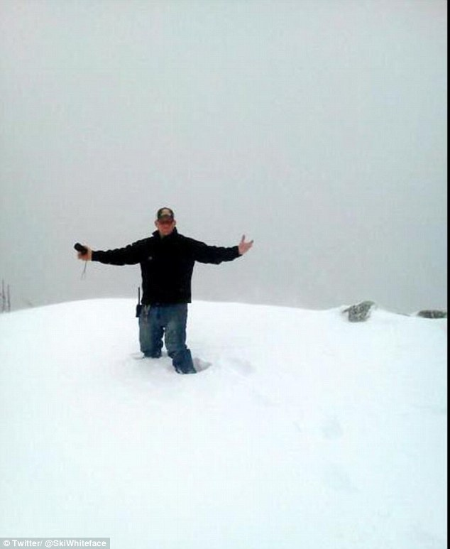 Knee-deep: An employee stands up to his knees in snow that fell Sunday on Whiteface Mountain in Wilmington, New York