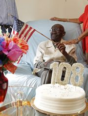Spring Valley resident Duranord Veillard, who will celebrate his 108th birthday on Saturday, holds the American and Haitian flags, while talking with his family, Feb. 26, 2015 in Spring Valley. (Photo: Tania Savayan/The Journal News)