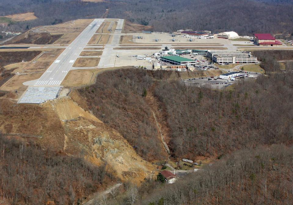 "This photo released by the West Virginia National Guard shows a landslide Thursday, March 12, 2015 near Yeager Airport in Charleston, W.Va. The landslide broke loose, taking out power lines, trees, an unoccupied home, as well as a church. It also caused a nearby creek to rise. No injuries were reported and no flights at the airport were affected. (AP Photo/West Virginia National Guard-Lt. Col. John ""Todd"" Harrell.)"