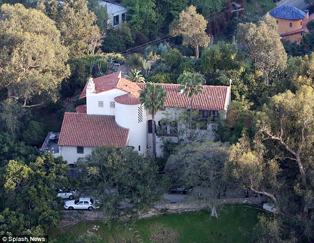 Cause unknown: Getty's ex-girlfriend called 911 around 2pm Tuesday afternoon. Paramedics who arrived on the scene found Getty unconscious with a 'traumatic injury to the rectal area' and significant bleeding.  Above, Investigators gather outside Getty's home in the Hollywood Hills on Tuesday