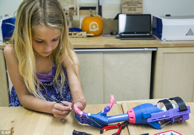 She doesn't need any help: Faith Lennox, 7, right, smiles as she holds an extra plastic prosthetics part with her newly 3-D printed hand at the Build it Workspace in Los Alamitos, California on Tuesday