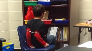A boy is seen restrained with handcuffs by a sheriff's deputy in a video released by the ACLU. (Photo: YouTube/ACLU)