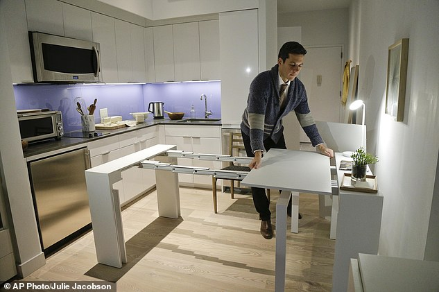"""In this Dec. 22, 2015, photo, Stage 3 Properties co-founder Christopher Bledsoe demonstrates a desk that expands into a dining table that can seat up to 12 people inside one of the apartments at the Carmel Place building in New York. As the city-sponsored """"micro-apartment"""" project nears completion, it's setting an example for tiny dwellings that the nation's biggest city sees as an aid to easing its affordable housing crunch. (AP Photo/Julie Jacobson)"""