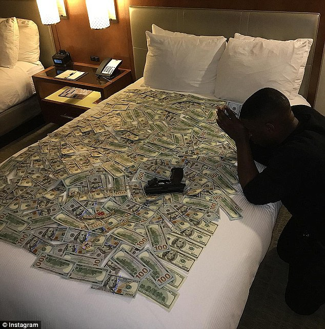 An image on Blac Youngsta's Instagram account shows $100 bills and a gun on a bed