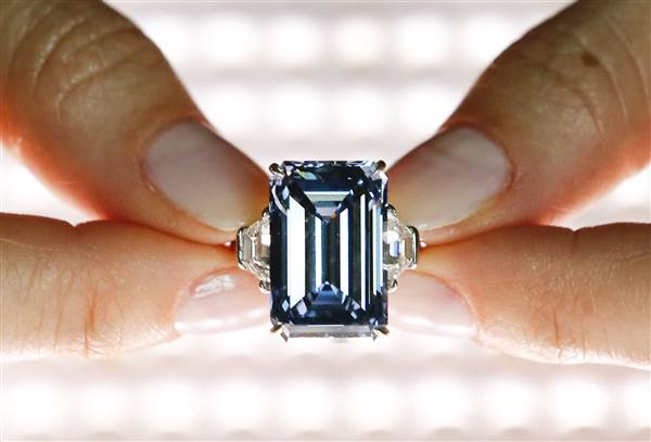 """A Christie's employee poses with the 14.62 carats Oppenheimer Blue diamond during a preview in Geneva, Switzerland on May 12, 2016. The largest """"fancy vivid blue"""" diamond is estimated to sell for from US$ 38 to 45 million when auctioned during the Magnificent Jewels auction in Geneva on May 18. Denis Balibouse / Reuters, file"""