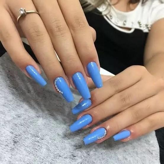 Unhas longas e quadradas com esmalte azul claro