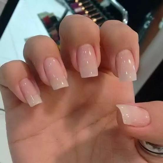 Unhas da mão quadradas e com um esmalte claro e transparente