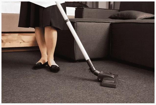 retrato recortado de mulher em uniforme de empregada, limpando o chão com aspirador
