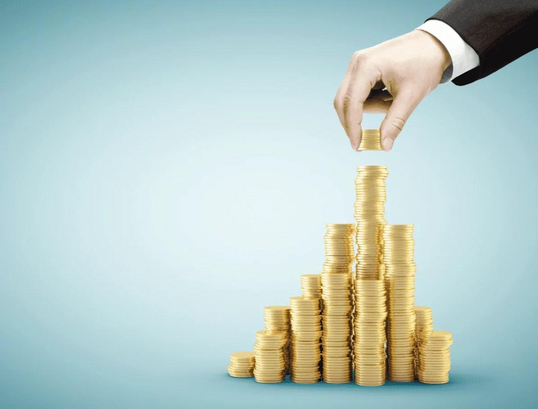Foto mostra uma mão acrescentando moedas em uma pilha de moedas.