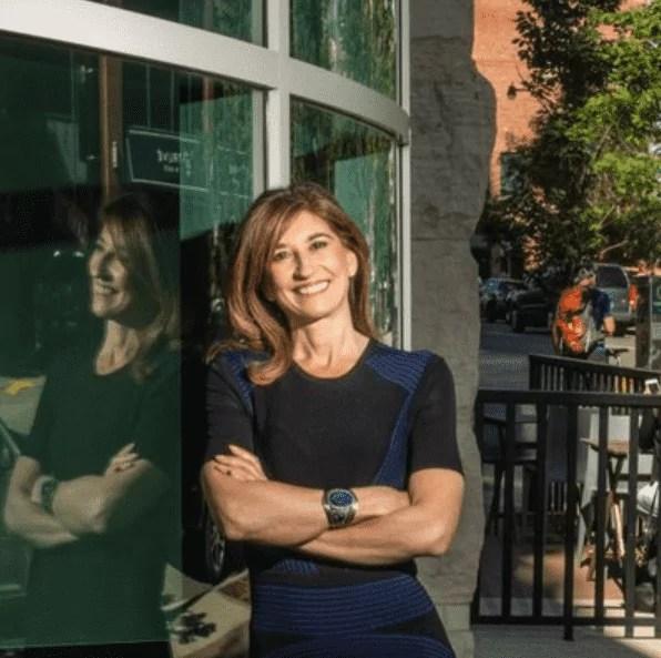 Foto mostra mulher adulta usando vestido preto, encosta em uma porta de vidro.