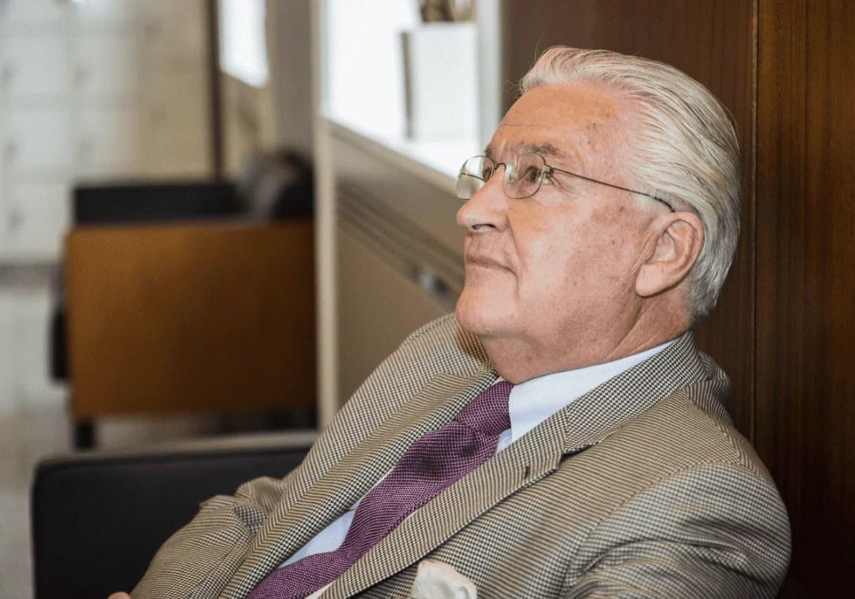 Foto do ex-milionário sentado de perfil. Homem branco, vestindo terno e usando óculos, de cabelos brancos.