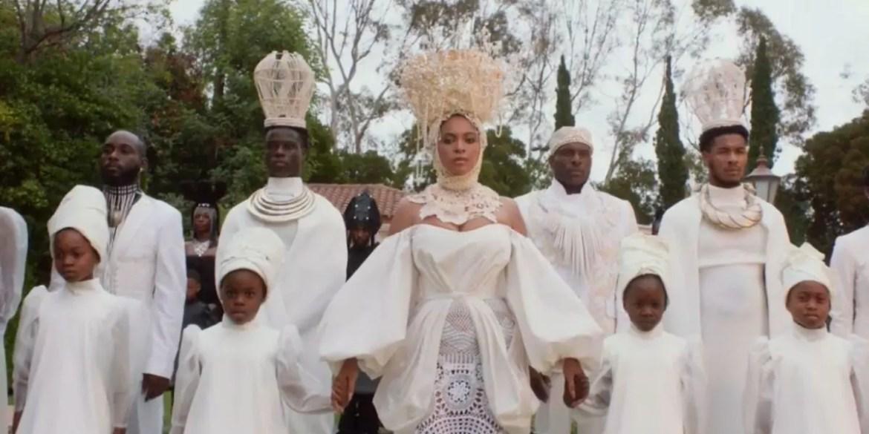 Beyoncé de branco rodeada de pessoas em cena do clipe do filme Black is King