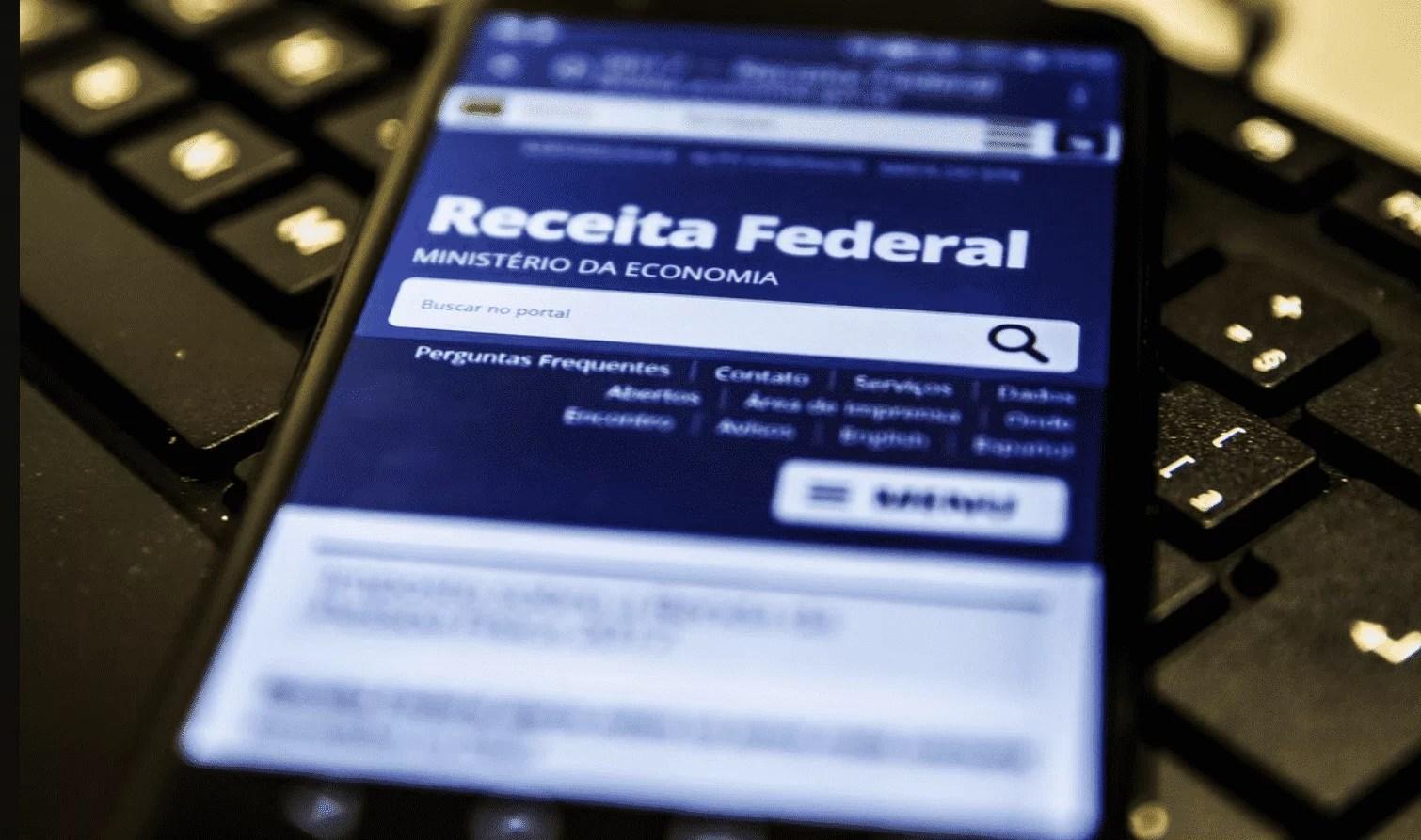 Celular com site da receita federal aberto, em cima de um teclado.