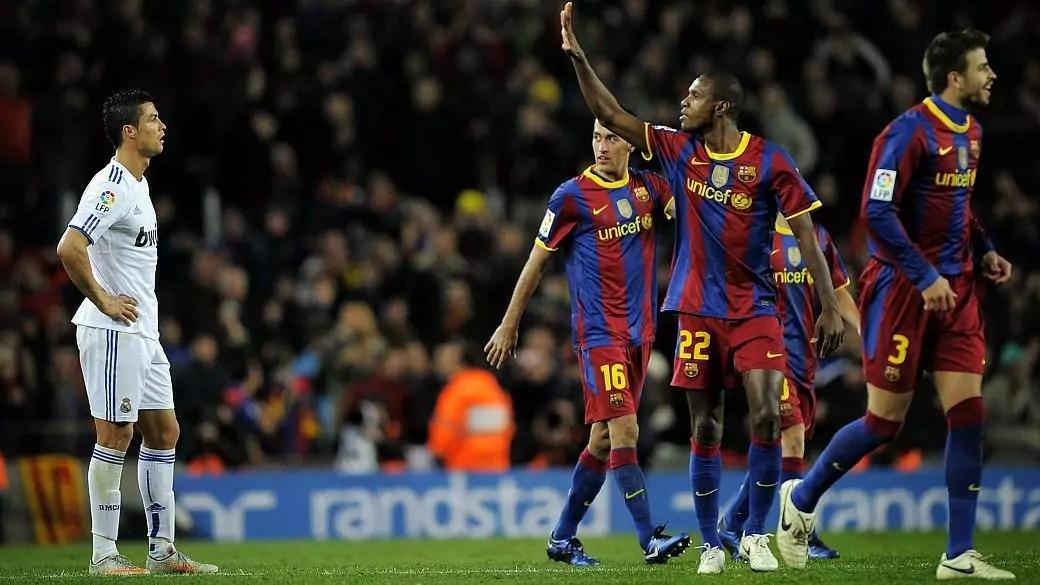 Imagem mostra eric Abidal comemorando gol do barcelona com Cristiano Ronaldo de fundo