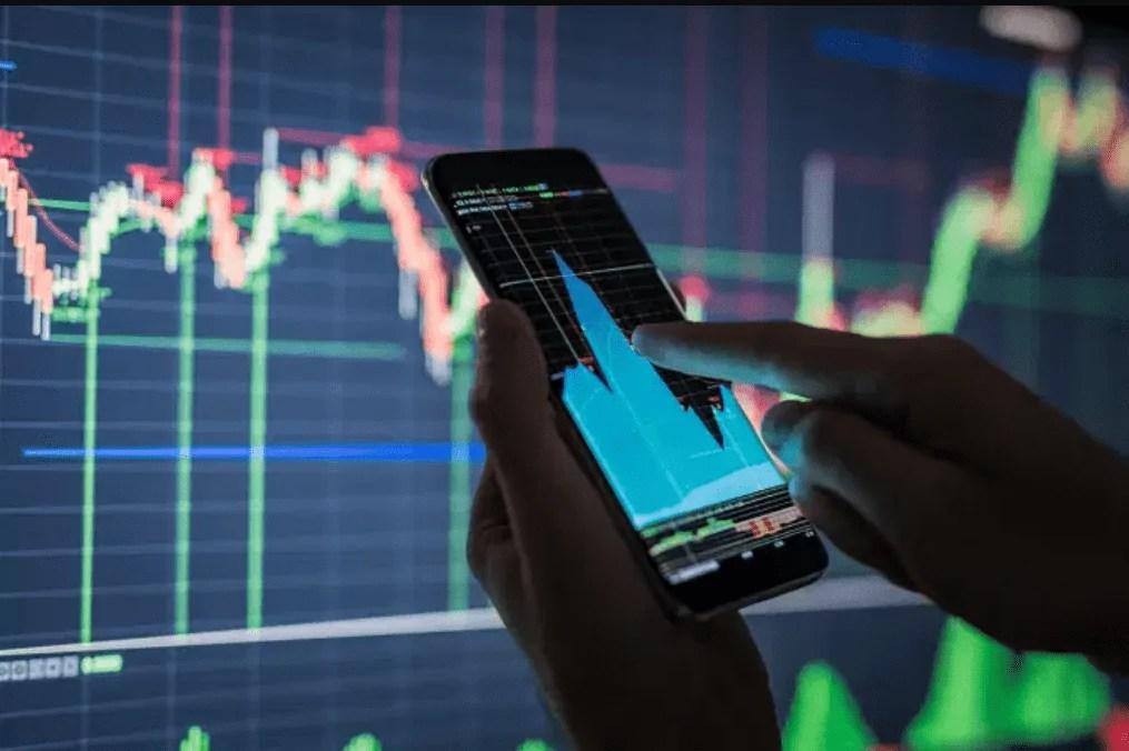 Pessoa mexendo no celular com gráfico aberto e na frente uma tela grande também com gráficos. onde investir