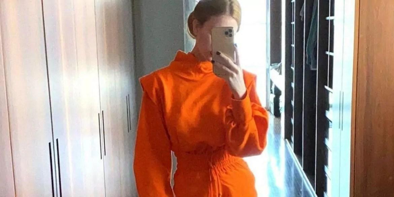 Marina Ruy Barbosa de roupa laranja tirando foto de frente para o espelho
